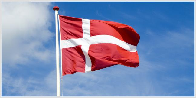 The Danish flag flies over the skies of Copenhagen, Denmark.