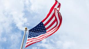 An American flag flies from a flagpole against a blue sky