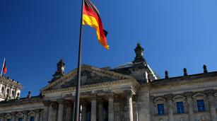 The German flag flies over the Reichstag Building in Berlin, where the Bundestag, the national parliament of Germany, is seated.
