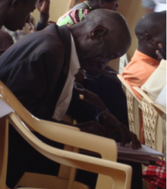 Farmer taking notes during the June District Dialogue Meeting in Mityana