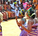 Women from Ghana dance at an event to raise community awareness about healthy behaviors.